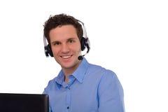 Lycklig lyckad ung affärsman med anteckningsboken och hörlurar med mikrofon Arkivbilder