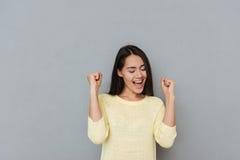Lycklig lyckad ung kvinna som ropar och firar framgång arkivfoto
