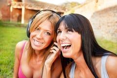 Lycklig lyssnande musik för flickavänner Arkivfoton