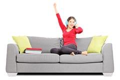 Lycklig lyssnande musik för kvinnlig student som placeras på en soffa arkivbild