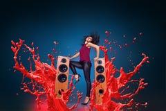 Lycklig lyssnande musik för ung kvinna med högtalare royaltyfri bild