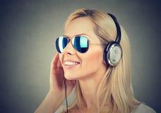 lycklig lyssnande musik till kvinnabarn Arkivbild