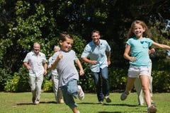 Lycklig mång- utvecklingsfamilj som springer in mot kamera royaltyfri bild