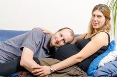 Lycklig make som omfamnar hans gravida fru på soffan Royaltyfri Foto