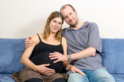 Lycklig make som omfamnar hans gravida fru på soffan Royaltyfria Foton