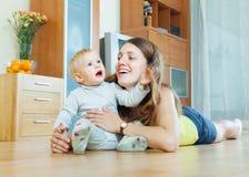 Lycklig mamma med barnet på trägolv Arkivbilder