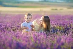 Lycklig mamma med den gulliga sonen på lavendelbakgrund Härlig kvinna och pojke i ängfält Lavendellandskap med damen och ungen arkivfoton
