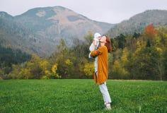 Lycklig mamma med hennes barn på naturen på hösttid Arkivfoto