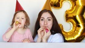 Lycklig mamma och barn på födelsedagpartiet Fostra hennes dotterleenden och laughes på en vit bakgrund 3 år Familj och arkivfilmer