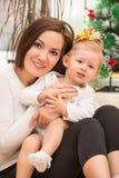 Lycklig mamma- och barnflicka som hemma kramar och skrattar. Begreppet av gladlynt barndom och familjen. Royaltyfri Fotografi