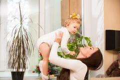Lycklig mamma- och barnflicka som hemma kramar och skrattar. Begreppet av gladlynt barndom och familjen. Arkivfoton