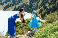 Lycklig mamma- och barnflicka som kramar på naturen begreppet av barndom, och famiy Arkivbild