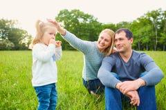 Lycklig mamma och farsor och dotter på gräset i parkera familj royaltyfri fotografi