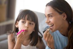 Lycklig mamma- och ungedotter som har gyckel som tillsammans gör makeup arkivbild