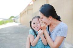 Lycklig mamma som viskar något som är hemlig till hennes lilla dotteröra Moder- och ungekommunikationsbegrepp arkivbilder