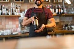 Lycklig man eller bartender med flaskan av vin på stången Royaltyfri Foto