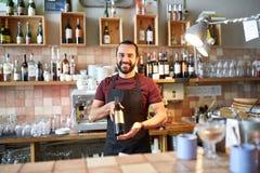 Lycklig man eller uppassare med flaskan av rött vin på stången Arkivfoto