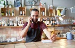 Lycklig man eller uppassare på stången som kallar på smartphonen Arkivbild