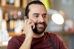 Lycklig man eller uppassare på stången som kallar på smartphonen Royaltyfri Foto