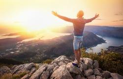 Lycklig man i bergen som ser solnedgången royaltyfria bilder