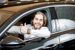 Lycklig man i en ny bil på visningslokalen royaltyfri foto