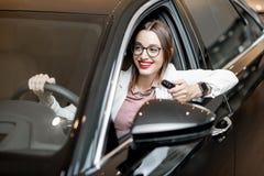 Lycklig man i en ny bil på visningslokalen arkivbilder