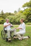 Lycklig man i en rullstol som talar med hans sjuksköterska som beside knäfaller Royaltyfria Foton