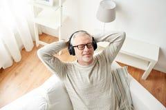 Lycklig man i hörlurar som hemma lyssnar till musik royaltyfria foton