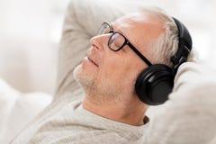 Lycklig man i hörlurar som hemma lyssnar till musik arkivbild