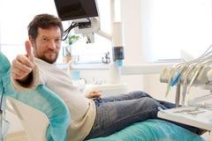 Lycklig man i tandläkarestudio efter operation Royaltyfria Bilder
