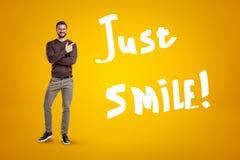 Lycklig man i tillfällig kläder med det RÄTTVISA LEENDEtecknet på gul bakgrund arkivfoto