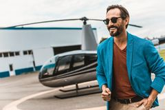 Lycklig man i tillfällig kläder som står nära helikoptern och le arkivfoton