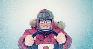 Lycklig man i vinterkläder med ett styrninghjul, snöhäftig snöstorm Begreppsbilchaufför Royaltyfri Foto