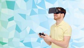 Lycklig man i virtuell verklighethörlurar med mikrofon med gamepad Royaltyfri Foto