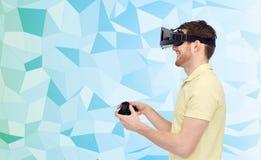 Lycklig man i virtuell verklighethörlurar med mikrofon med gamepad Arkivbild
