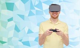 Lycklig man i virtuell verklighethörlurar med mikrofon med gamepad Royaltyfria Bilder