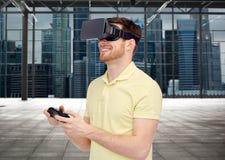 Lycklig man i virtuell verklighethörlurar med mikrofon med gamepad Fotografering för Bildbyråer