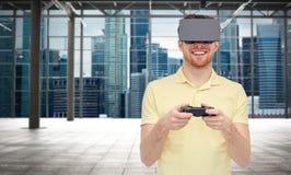 Lycklig man i virtuell verklighethörlurar med mikrofon med gamepad Royaltyfria Foton