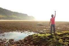 Lycklig man med armar som lyfts på stranden arkivbild