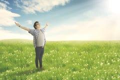 Lycklig man med den öppna tyckande om våren för armsned boll på blomningäng Royaltyfri Fotografi