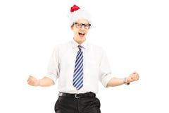 Lycklig man med den santa hatten som gör en gest lycka Royaltyfri Fotografi