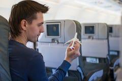 Lycklig man med flygplanet för liten modell inom ett stort Arkivfoton