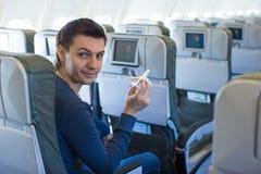 Lycklig man med flygplanet för liten modell inom ett stort flygplan Arkivbild