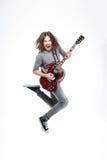 Lycklig man med långt hår som hoppar och spelar den elektriska gitarren arkivbild