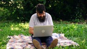 Lycklig man med oudoors för en dator Den stiliga hipsteren som använder bärbara datorn parkerar in, på en sommardag bärbar dator  stock video