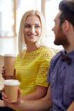Lycklig man och kvinna som i regeringsställning dricker kaffe Arkivbild