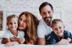 Lycklig man och kvinna som lägger på säng med ungar royaltyfria bilder