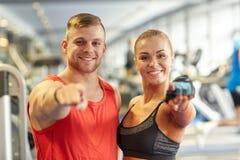 Lycklig man och kvinna som pekar fingret till dig i idrottshall Royaltyfria Bilder