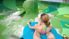 Lycklig man och kvinna som rider ner vattenglidbanan Folket som har gyckel i vatten, parkerar på semesterort under sommarsemester arkivfilmer