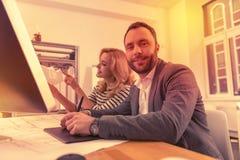 Lycklig man och kvinna som sitter på ett skrivbord som diskuterar tillsammans deras arbetsdag royaltyfria bilder